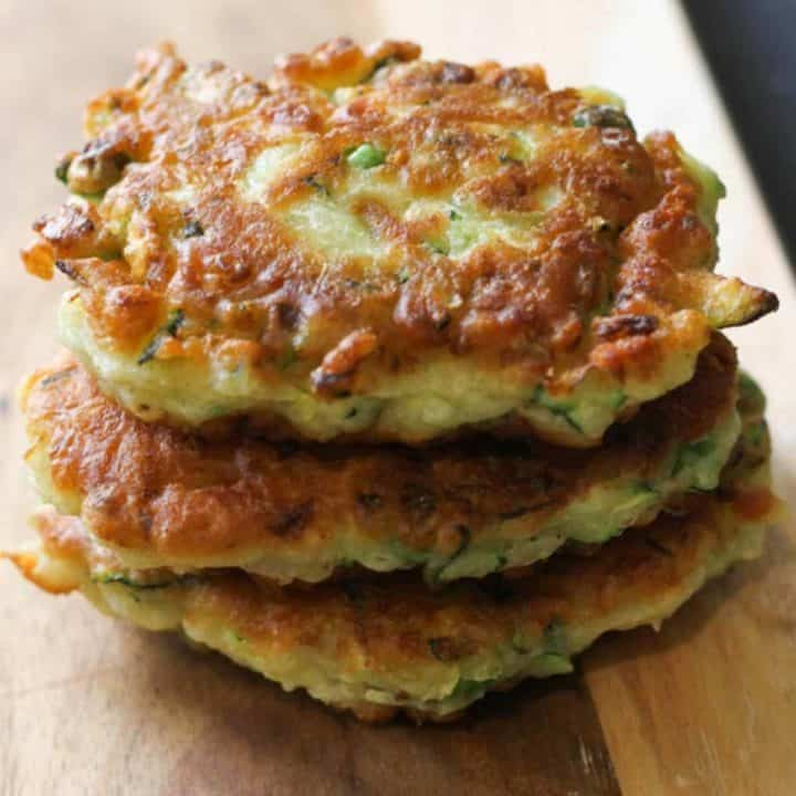 pea & feta fritters stacked on top of each other on a wooden serving board.