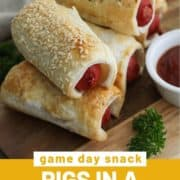 """puffy dogs stacked on a wooden serving board with text overlay """"pigs in a blanket""""."""