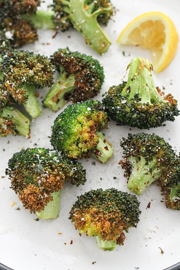roasted broccoli on a white plate with lemon wedges.