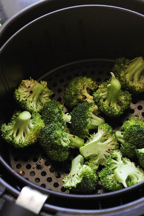 broccoli inside an air fryer basket.