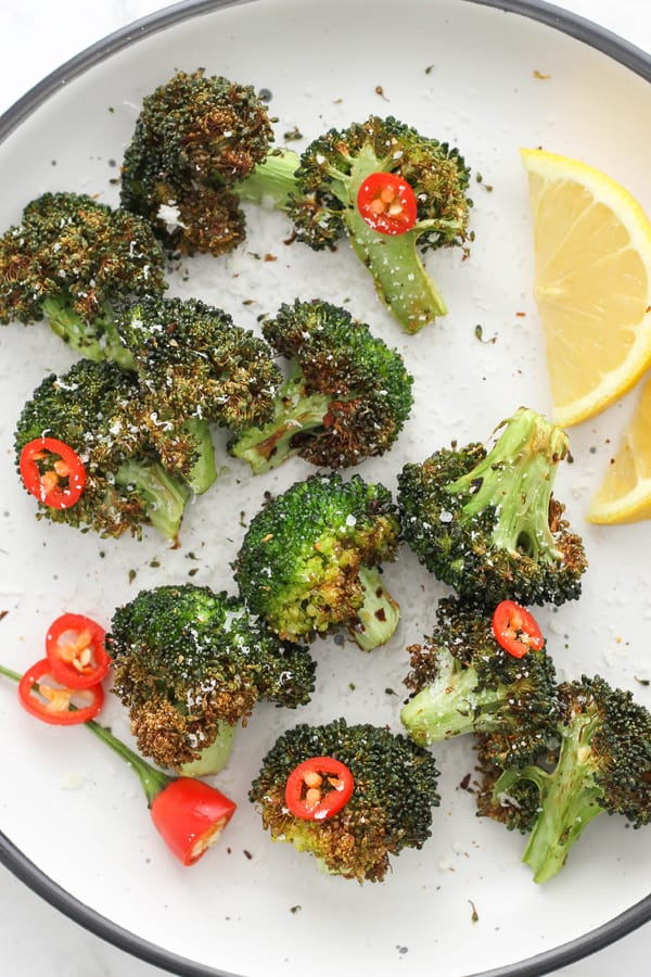 roasted broccoli on a white plate with lemon wedges and chopped chilli.