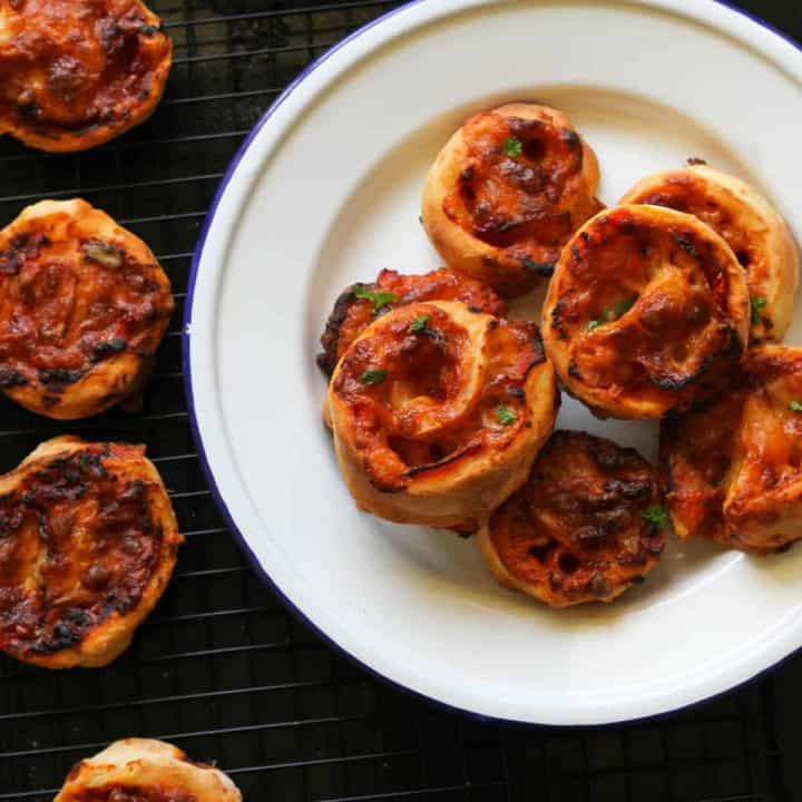 pizza pinwheels piled up on a white plate.