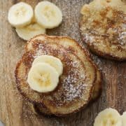"""mini pancakes stacked on top of each other on a wooden board with text overlay """"banana pikelets""""."""