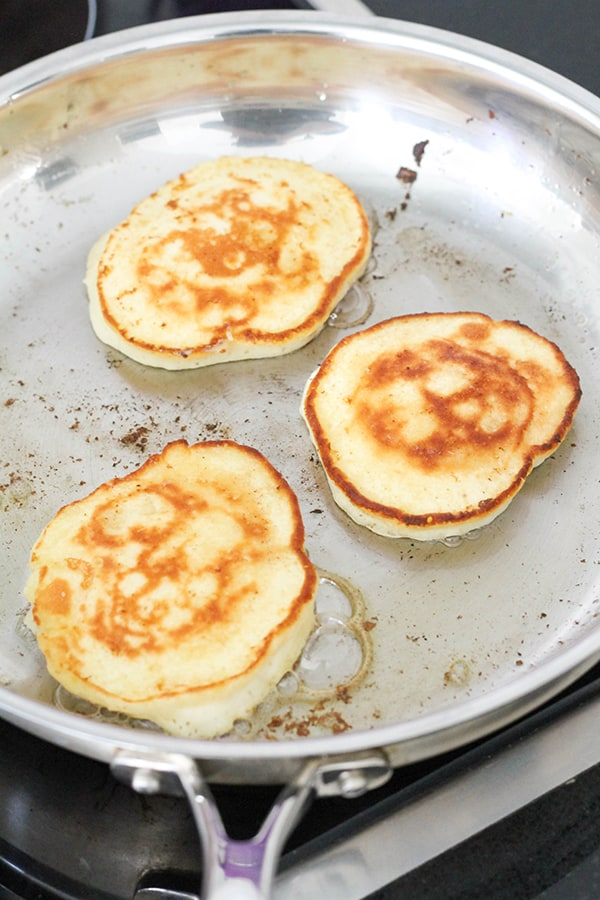 pikelets cooking in a frying pan.