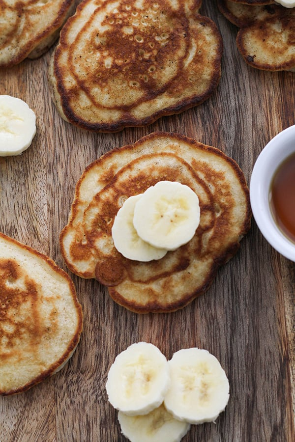 pikelets spread out across a wooden board, topped with banana.