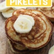"""mini pancakes stacked on top of each other on a wooden board with text overlay """"easy banana pikelets""""."""