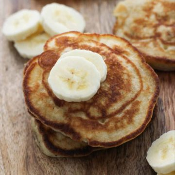 banana pikelets stacked on top of each other on a wooden board.