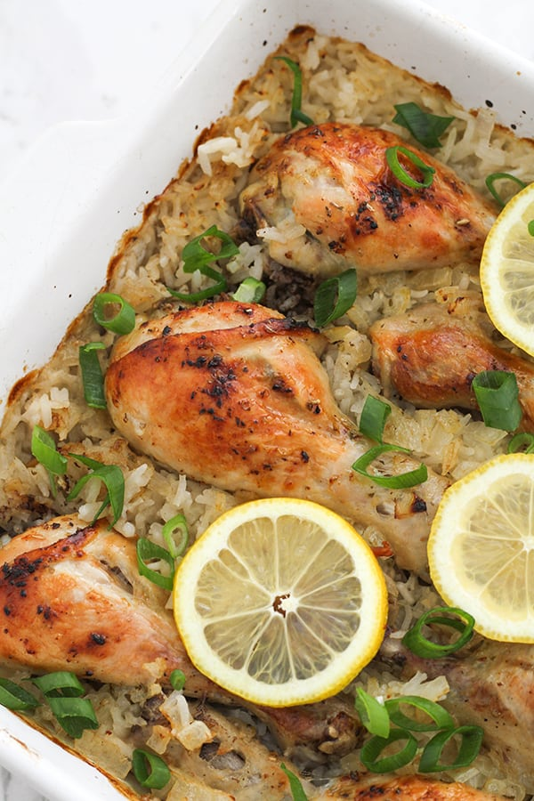 chicken drumsticks on top of a bed of rice in a baking dish, topped with lemon slices.