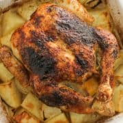 "roast chicken and potatoes in a white baking dish with text overlay ""Greek roast chicken""."