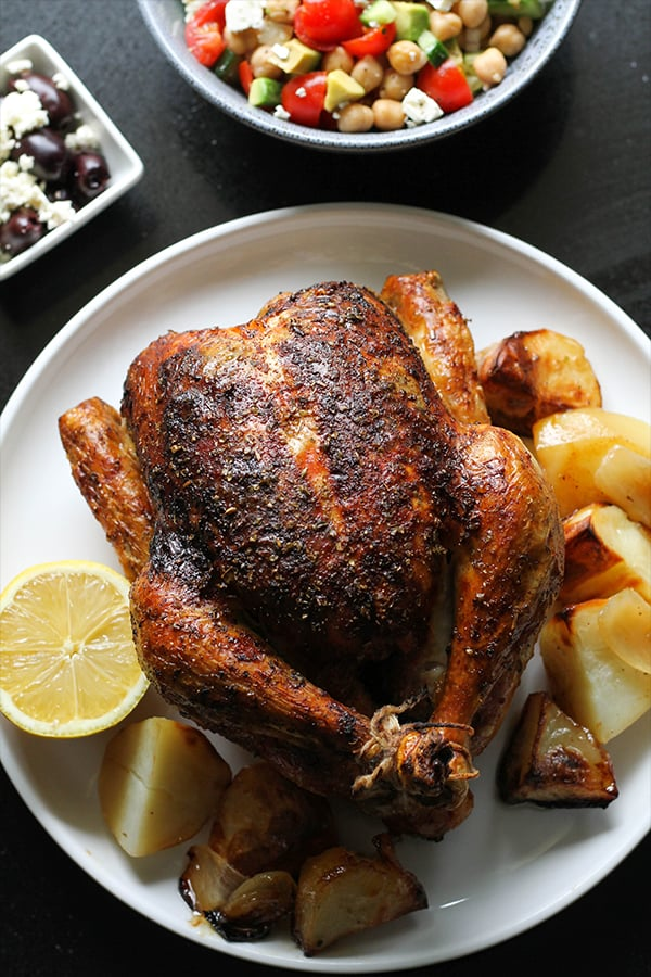 greek roast chicken and potatoes on a white plate.