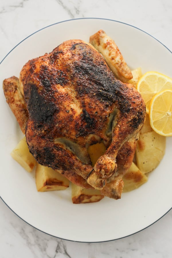 roast chicken and potatoes on a white plate.