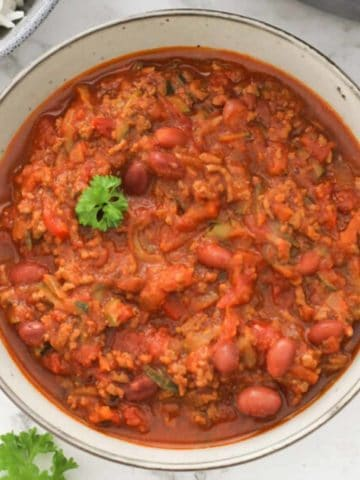 a bowl of chilli con carne topped with parsley.