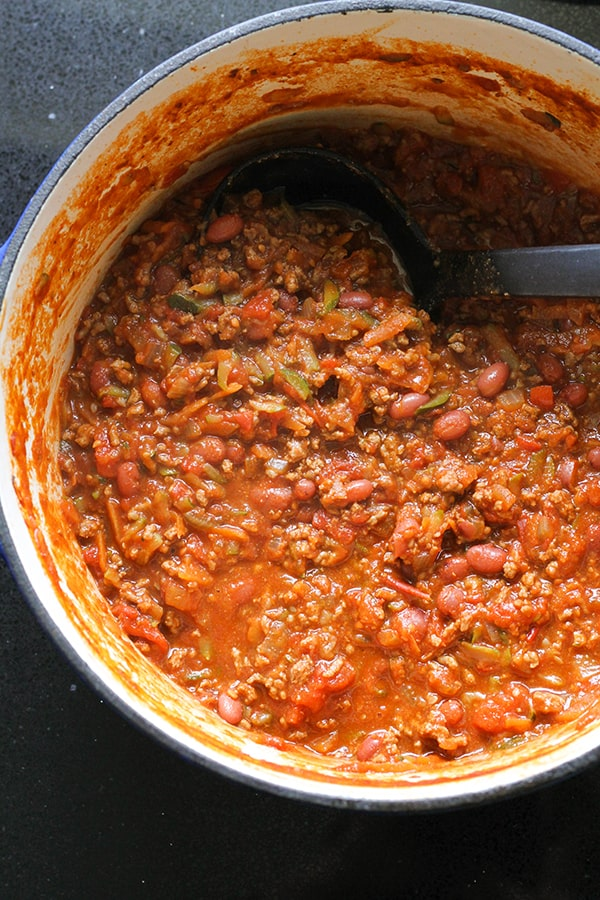 a large pot of chilli con carne with a ladle submerged into the chilli.