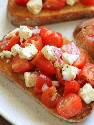 tomato and feta bruschetta on a white plate.