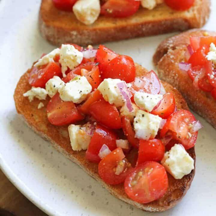 tomato and feta bruschetta on a white plate.