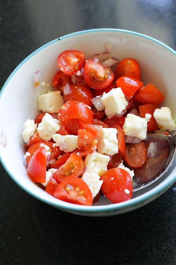 diced tomatoes, onion and feta in a bowl.