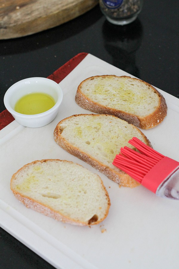 a pastry brush brushing oil over slices of bread.