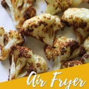 "roasted cauliflower on a white plate with text overlay ""air fryer roasted cauliflower""."