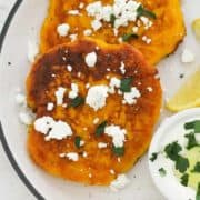 "two fritters on a white plate topped with feta and parsley with text overlay ""pumpkin fritters""."