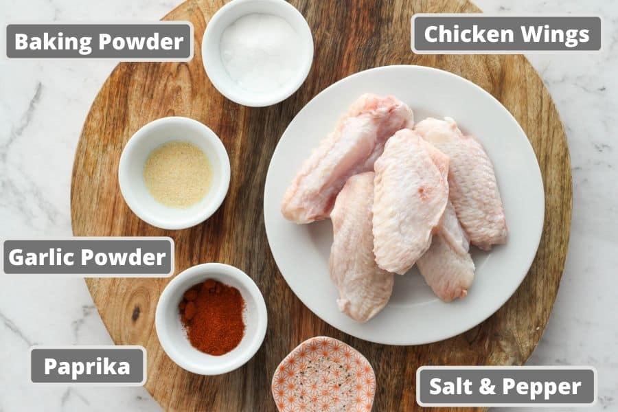 chicken wing ingredients on a wooden board, including baking powder, garlic powder etc.