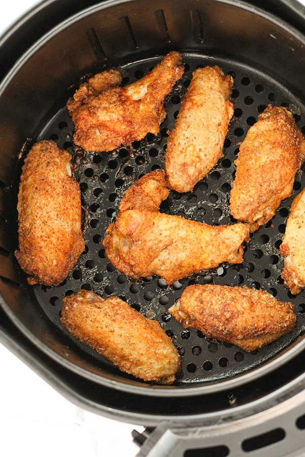 cooked chicken wings in an air fryer basket.