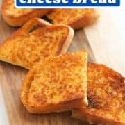 "slices of cheese toast on a wooden serving board with text overlay ""sizzler copycat cheese bread""."