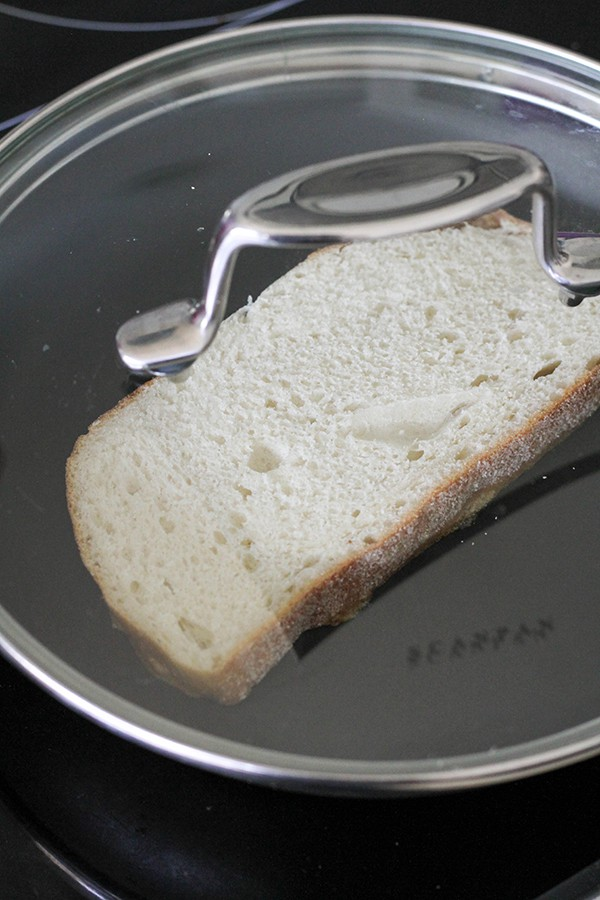 slice of bread in a skillet with a lid on top.