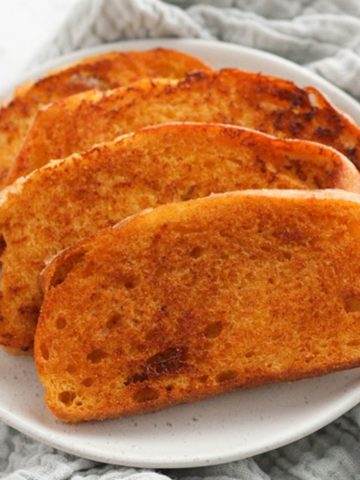 slices of cheese toast on a white plate.