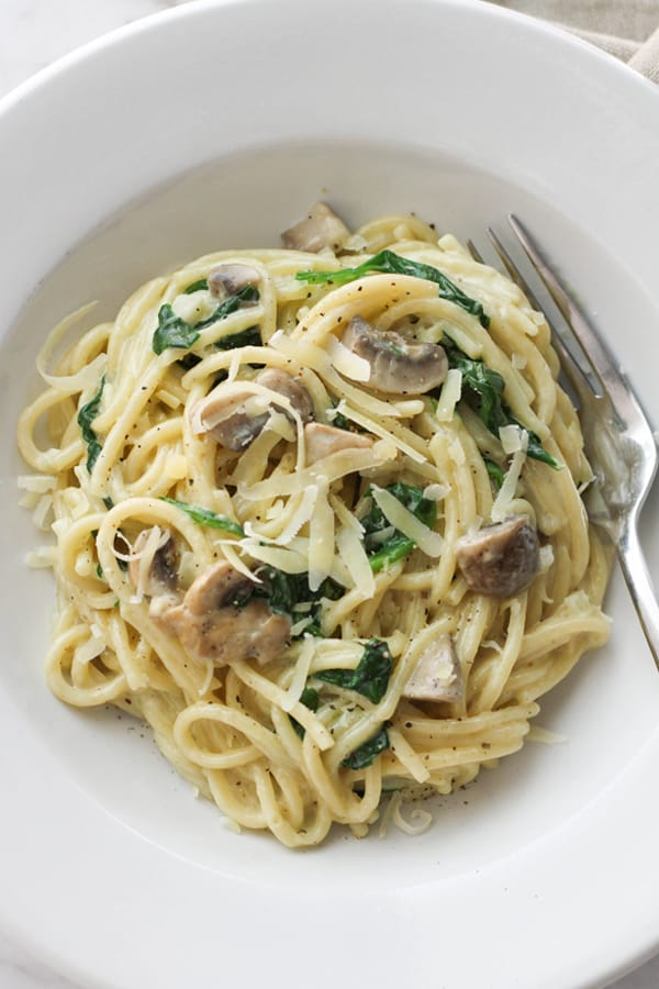 creamy spinach and mushroom pasta in a white bowl.