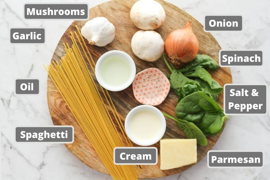 ingredients for spinach and mushroom pasta on a wooden board.