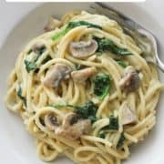 "pasta in a white bowl with text overlay ""creamy mushroom and spinach pasta""."