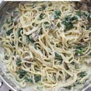 "pasta in a frying pan with text overlay ""creamy mushroom and spinach pasta""."