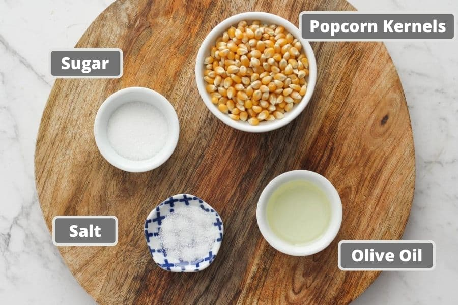 sweet and salty popcorn ingredients on a wooden board.