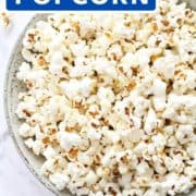 "popcorn in a grey bowl with text overlay ""sweet and salty popcorn""."