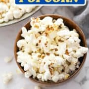 "popcorn in a brown bowl with text overlay ""sweet and salty popcorn""."