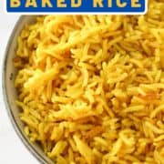 """yellow rice in a blue bowl with text overlay """"turmeric baked rice""""."""