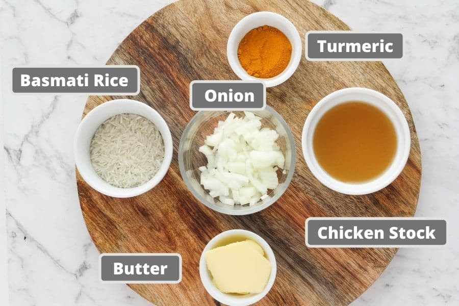 ingredients for turmeric rice on a wooden board, including rice, butter and chicken stock.