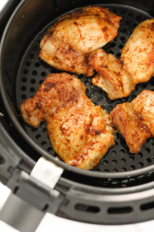 cooked chicken thighs in an air fryer basket.
