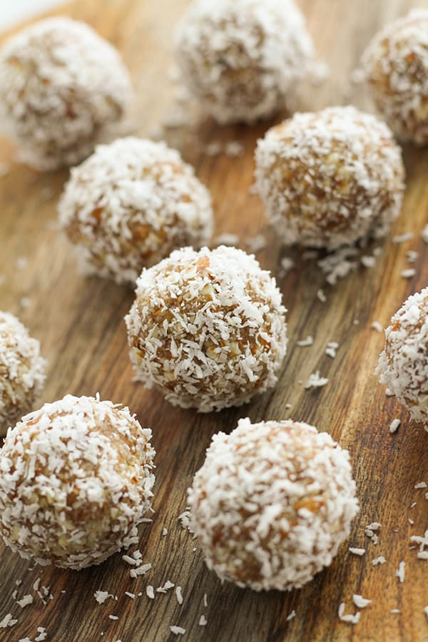 coconut date balls on a wooden board.