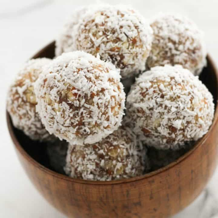 date coconut energy balls in a wooden bowl.