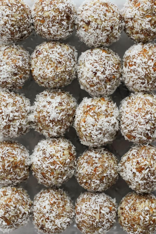 coconut date balls lined up together in a glass container.
