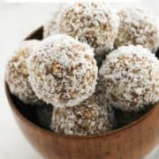 "energy balls in a wooden bowl with text overlay ""coconut + date energy balls""."