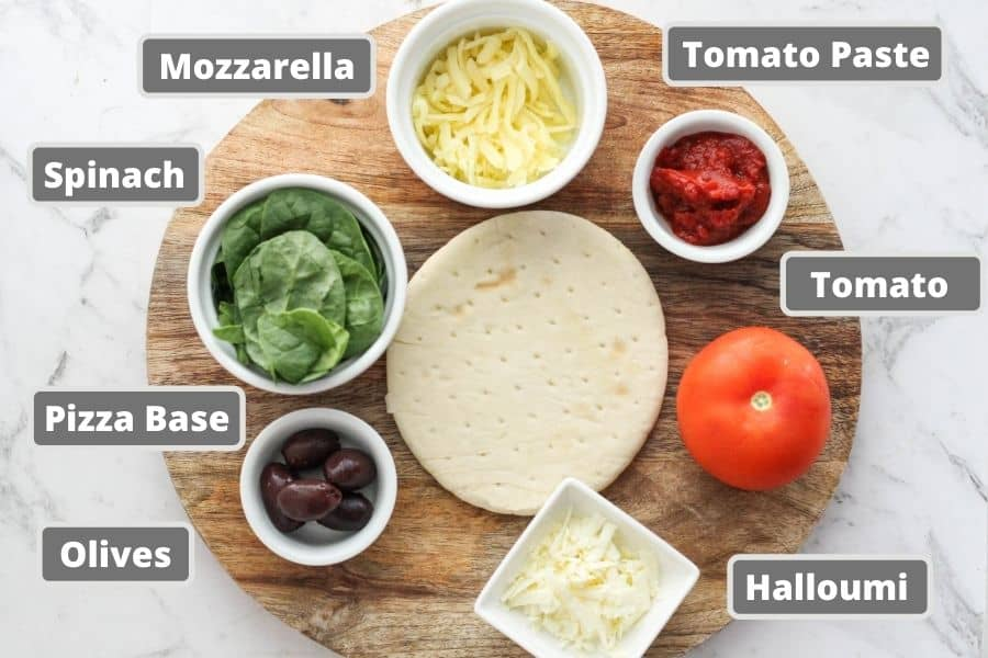 ingredients for pizza on a wooden board including halloumi, tomato, spinach and olives.