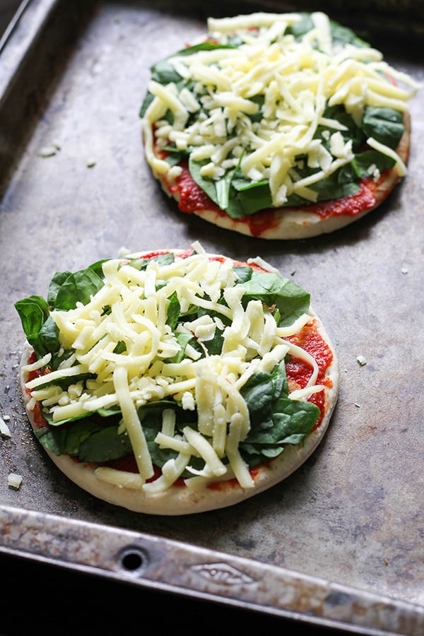 pizza bases on a baking tray covered with spinach and cheese.