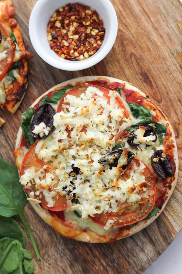 pizza topped with halloumi, spinach and tomato on a wooden serving board.