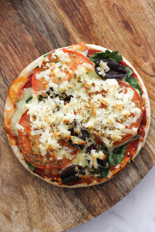 pizza topped with tomato, spinach and halloumi cheese on a wooden board.