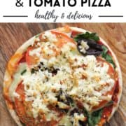 """pizza on a wooden serving board with text overlay """"halloumi, spinach and tomato pizza""""."""