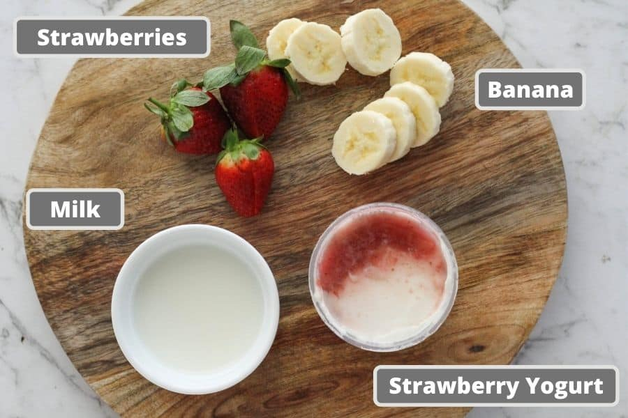 ingredients for strawberry smoothie including milk, yogurt, banana slices and strawberries.