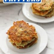 "stack of fritters on a plate with a bowl of potatoes in the background and text overlay ""potato fritters""."