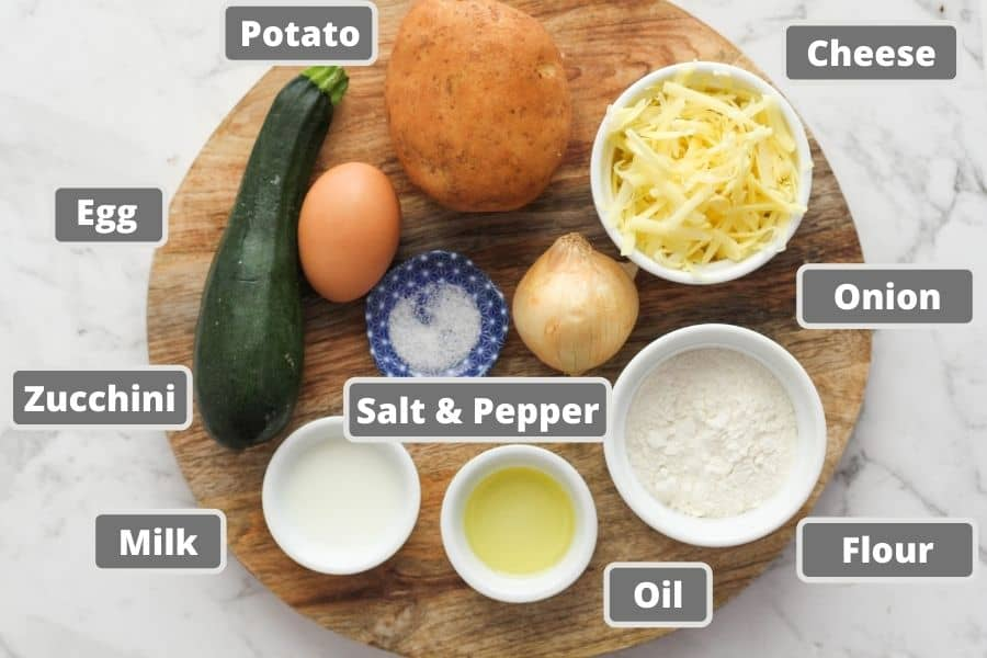 ingredients for potato fritters on a wooden board including egg, cheese and milk.